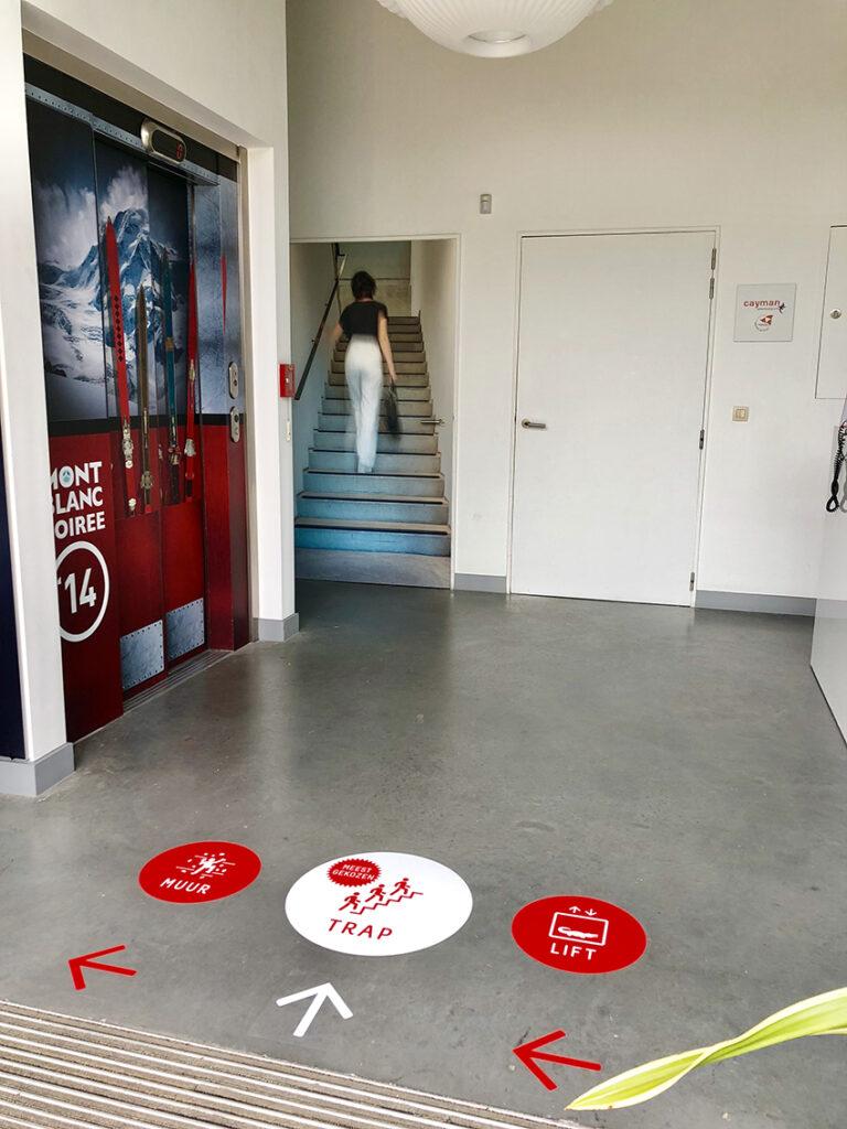Vloerstickers die de keuze tussen trap en lift aangeven in het Cayman-gebouw