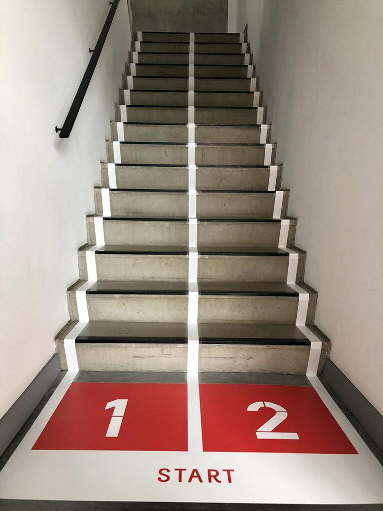 Vloersticker met 'Start' onderaan de trap in het Cayman-gebouw