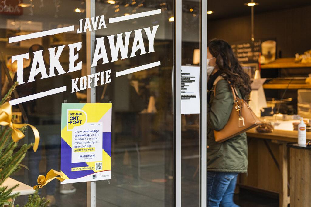 """Een affiche van de campagne """"Het Pand OntPopt"""" aan het raam van een lokale winkel in Waregem"""